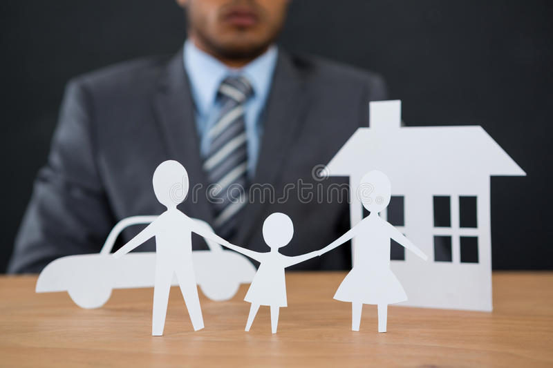 Paper cut out family chain with car and house at desk. Close-up of paper cut out family chain with car and house at desk stock images