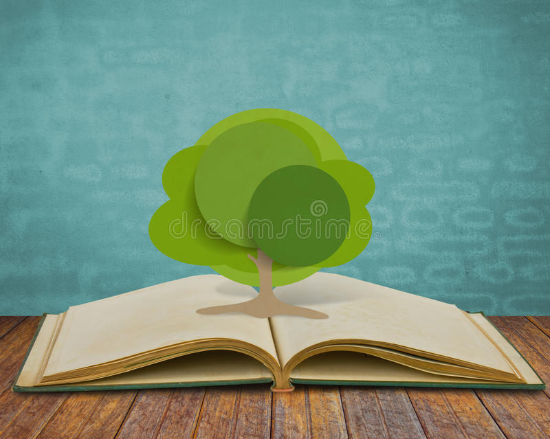 Paper cut of tree on old book. Design styles royalty free stock image
