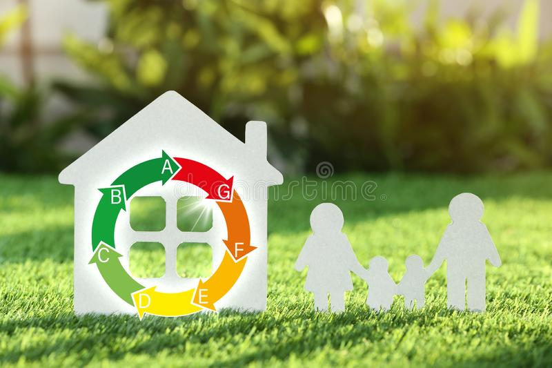 Paper cutout of family and house on fresh grass. Life insurance concept royalty free stock image