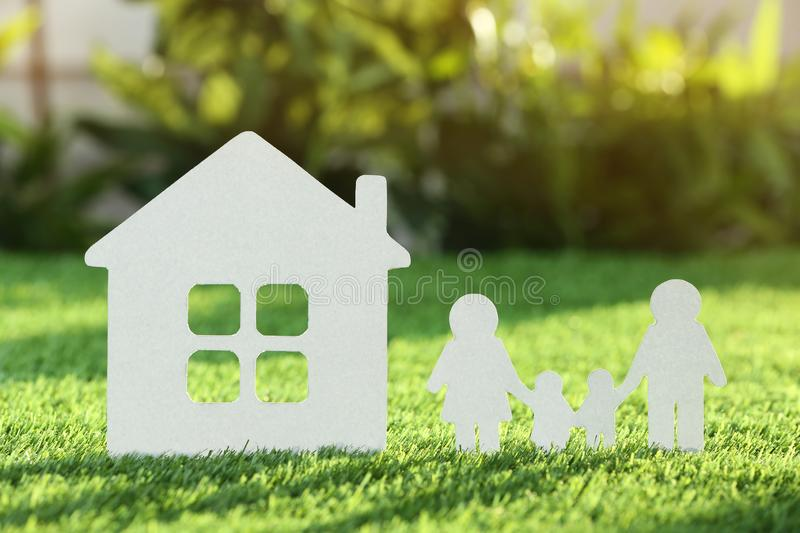 Paper cutout of family and house on fresh grass. Life insurance concept stock photos