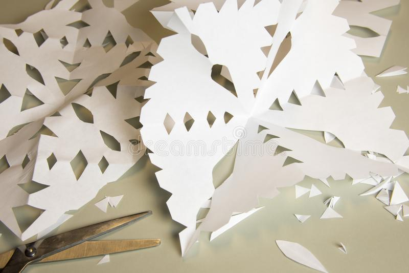 Paper cutout snowflakes project. Handmade paper cutout snowflakes arts and crafts project stock photo