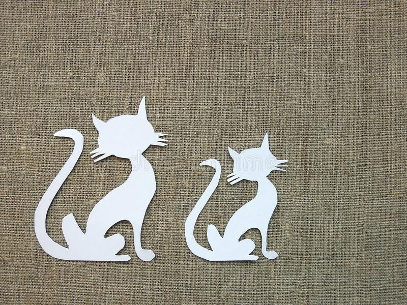 Paper cutting - white cats on linen fabric stock photography