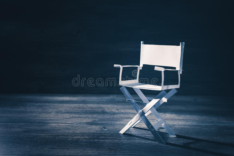 Paper director chair on a blueish grey background. High contrast image of director chair made of paper royalty free stock images