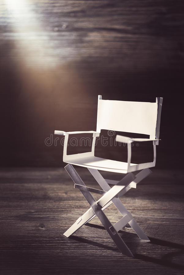 Paper director chair on a blueish grey background. High contrast image of director chair made of paper / selective focus royalty free stock images