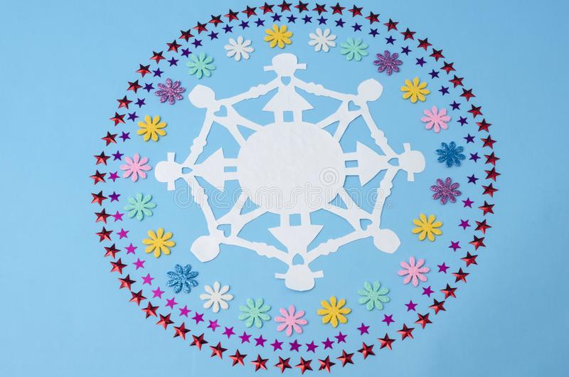 Paper doll chain and circles made from flowers and stars confetti stock images