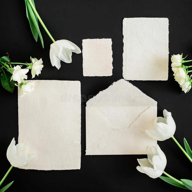 Paper envelop, white cards and flowers on black background. Flat lay, top view. Creative valentines day concept stock images