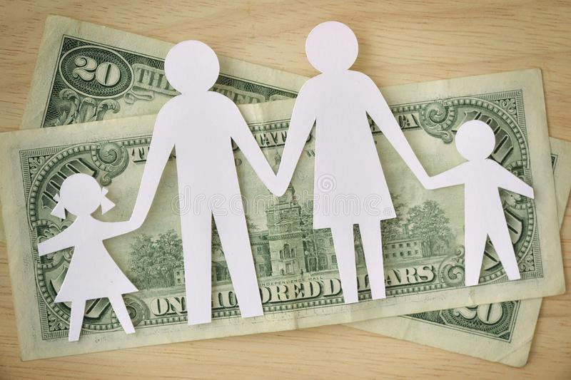 Paper family cut-out on dollars banknotes - Family budget concept royalty free stock photo
