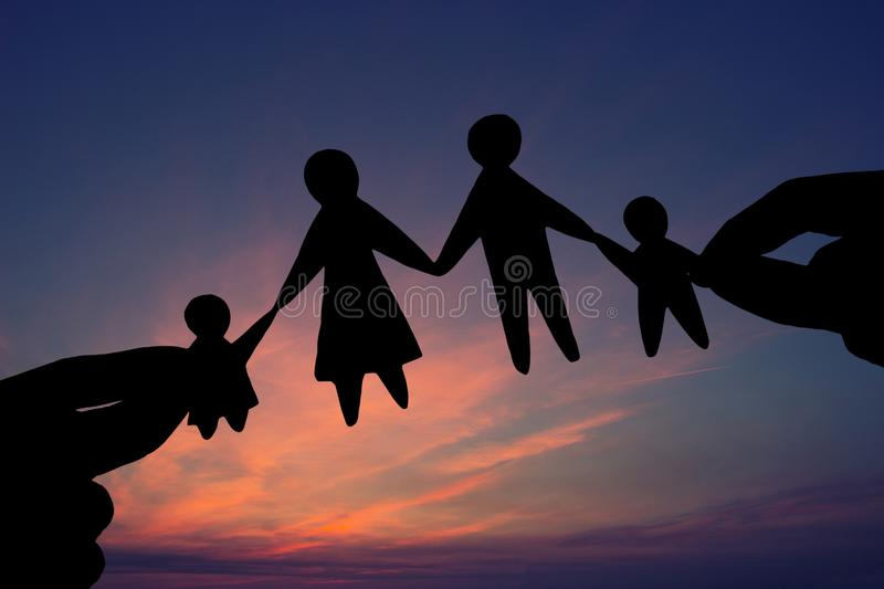 Paper family in two hands against the sky background royalty free stock photos
