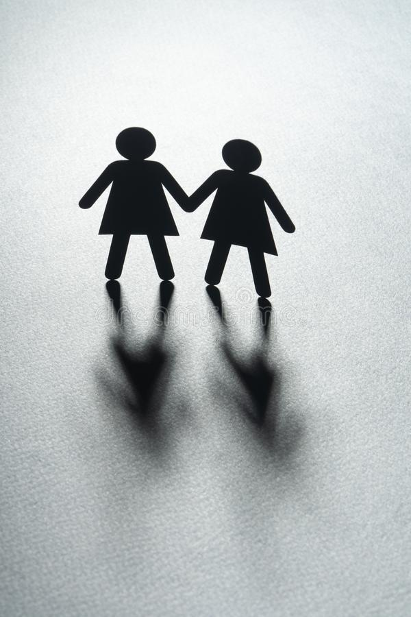 Black paper figure of a female couple holding hands on gray surface. Same-sex marriage, diversity, minorities concept. Paper figure of a female couple holding stock photography