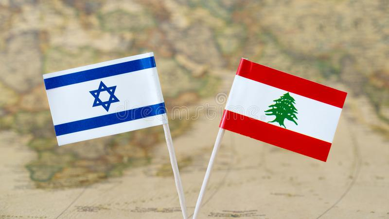 Israel and Lebanon flag pins on a world map, political or diplomatic relations concept. Paper flag pins of Israel and Lebanon on a world map background. Concept stock photos