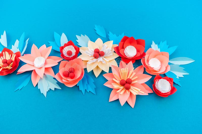 Paper flower for Christmas decor. Color coral fashion pastel. Handmade children's creativity. Blue background. Cozy new year stock image