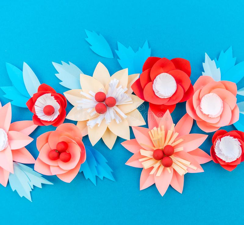Paper flower for Christmas decor. Color coral fashion pastel. Handmade children's creativity. Blue background. Cozy new year royalty free stock photography