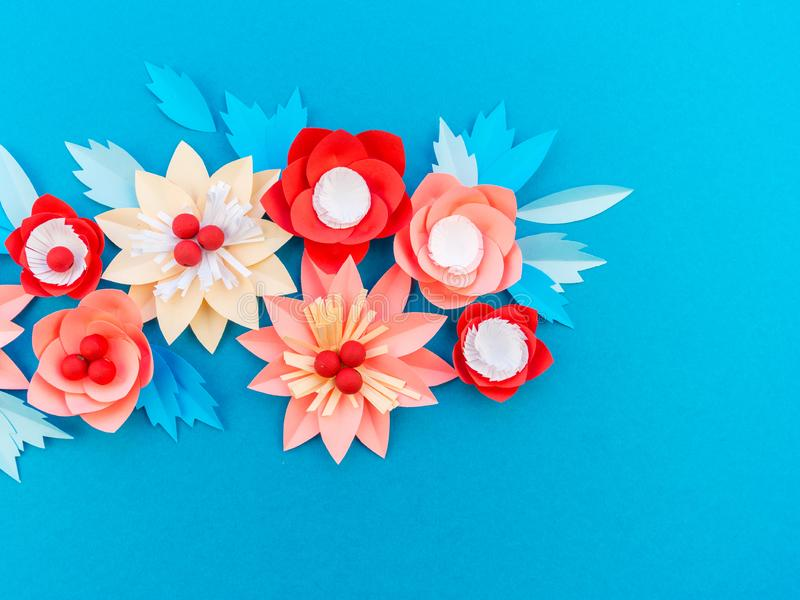 Paper flower for Christmas decor. Color coral fashion pastel. Handmade children's creativity. Blue background. Cozy new year royalty free stock photo