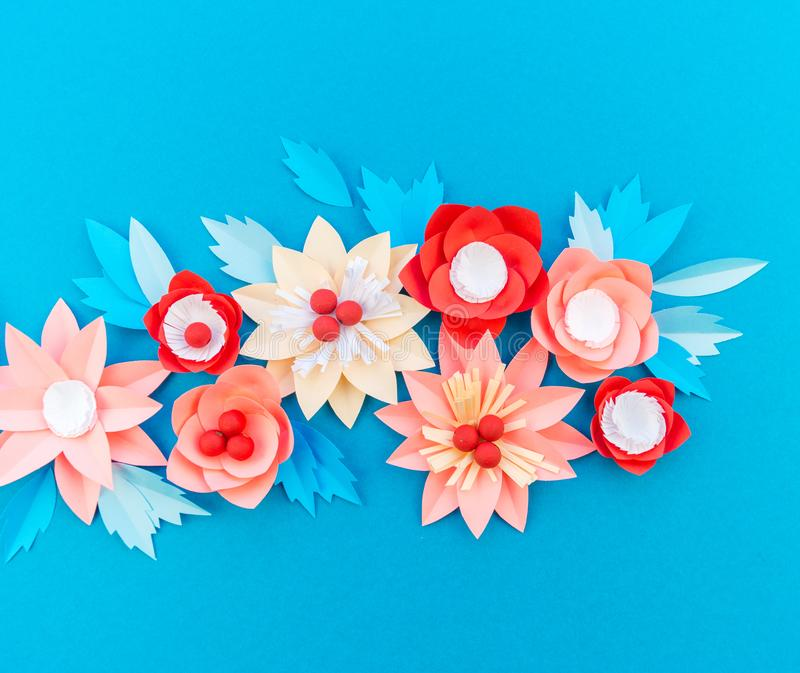 Paper flower for Christmas decor. Color coral fashion pastel. Handmade children's creativity. Blue background. Cozy new year stock photography
