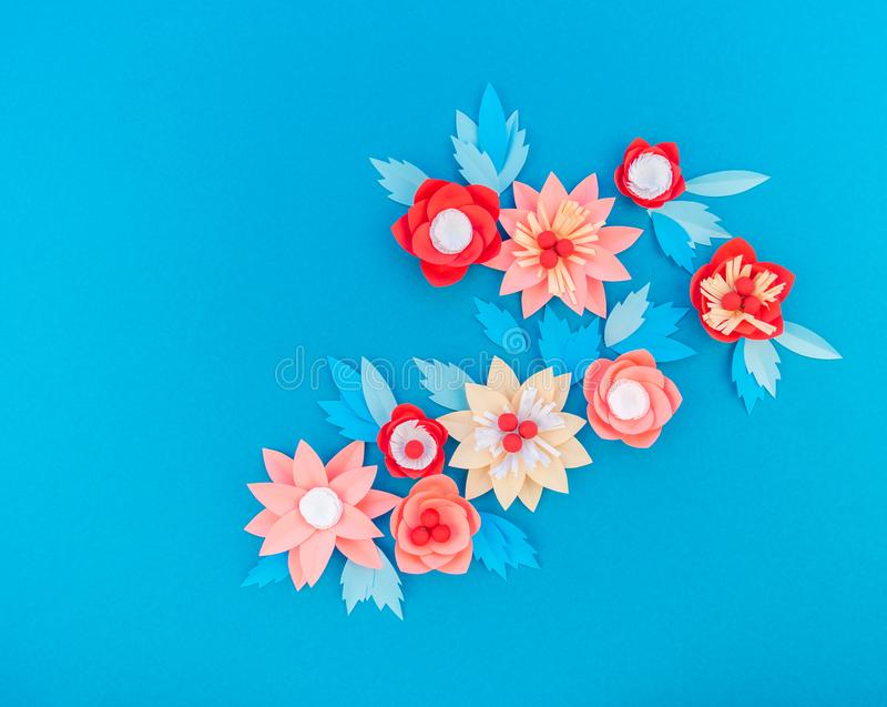 Paper flower for Christmas decor. Color coral fashion pastel. Handmade children's creativity. Blue background. Cozy new year royalty free stock image