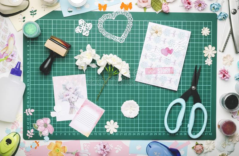 Paper flowers, a homemade card and tools for scrapbooking on the green mat for cutting. The view from the top, no hands stock photography