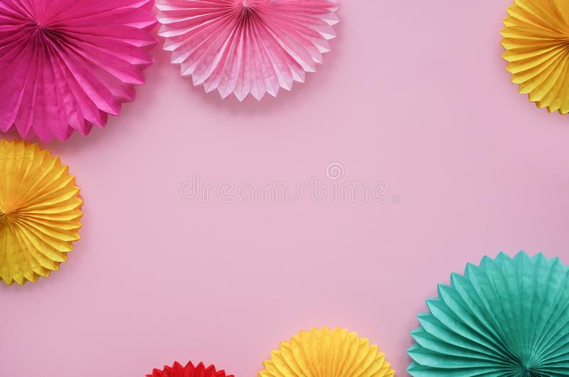 Paper flowers on pink table top view. Festive or party background. Flat lay style. Copy space for text. Birthday greeting card. royalty free stock photography