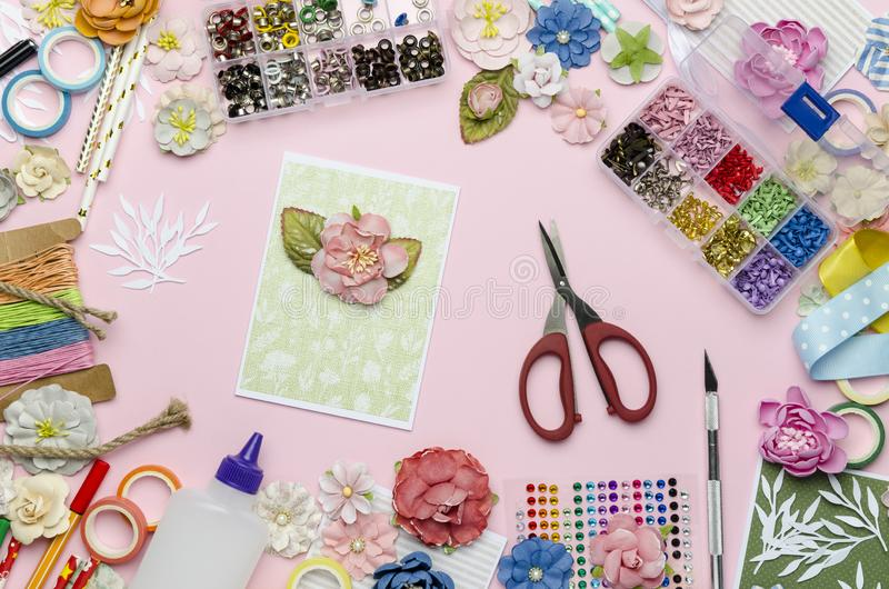 Paper flowers, scissors, homemade card, paper and scrapbooking items on pink background. Scrapbooking, top view royalty free stock photography