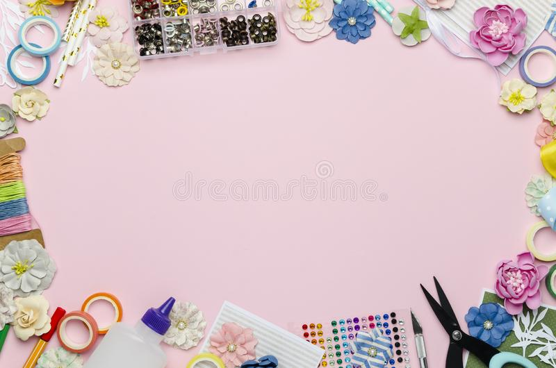 Paper flowers, scissors, paper and scrapbooking items on pink background. Scrapbooking, top view, empty space for text in the center stock images