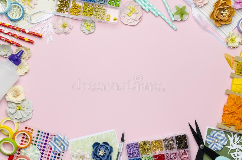 Paper flowers, scissors, paper and scrapbooking items on pink background. Scrapbooking, top view, empty space for text in the center stock image