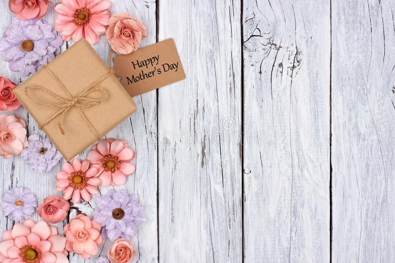 Paper flowers side border with Mother`s Day gift and tag over wood. Side border of paper flowers with Mother`s Day gift box and tag against a rustic white wood stock photo