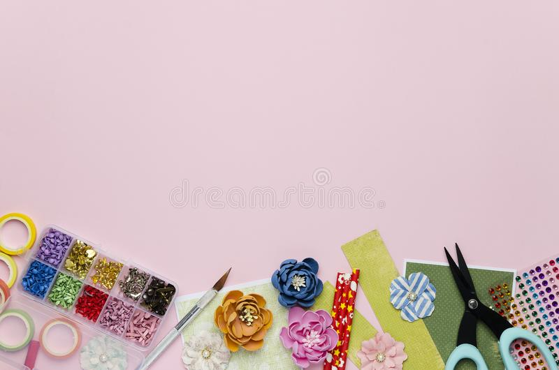 Paper flowers, tools, paper and scrapbooking items on pink background. Scrapbooking, top view, empty space for text stock image