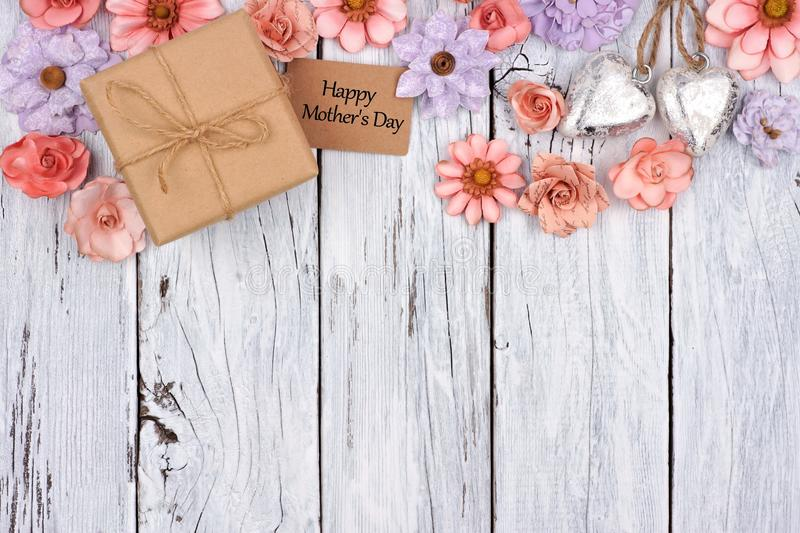 Paper flowers top border with Mother`s Day gift and tag over wood. Top border of paper flowers with Mother`s Day gift box and tag against a rustic white wood stock images