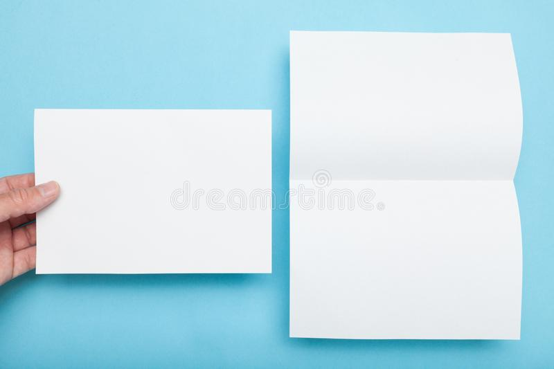 Paper flyer A5 mockup, man holding blank on blue background.  royalty free stock photos