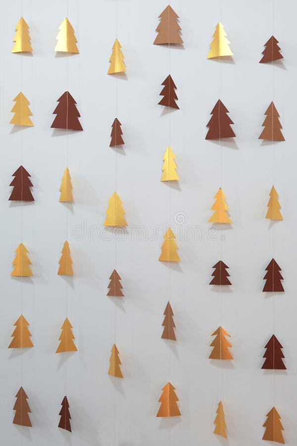 Paper garland of golden Christmas trees strung on a white thread. Designer background for decoration in the room. New Year`s wall royalty free stock photos