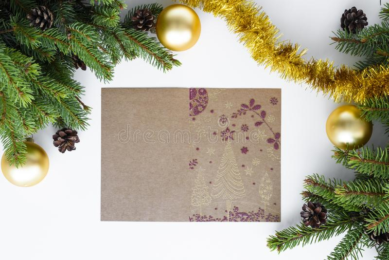 Paper greeting card with christmas elements. Copy space for greetings. Green conifer branches, cones, gold baubles and tinsel. Paper greeting card with stock images