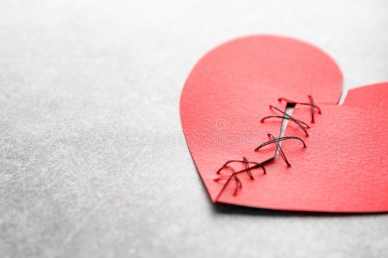 Paper heart cut in half and sewn back together. On light background. Relationship problems royalty free stock images