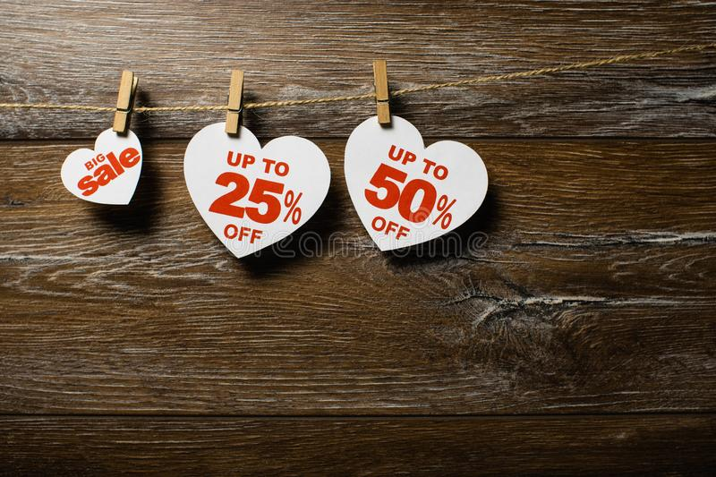 Paper hearts with discounts on the clothespins on the rope isolated on brown wooden background. Big sale 14 february. Three white hearts with discounts hang on stock image