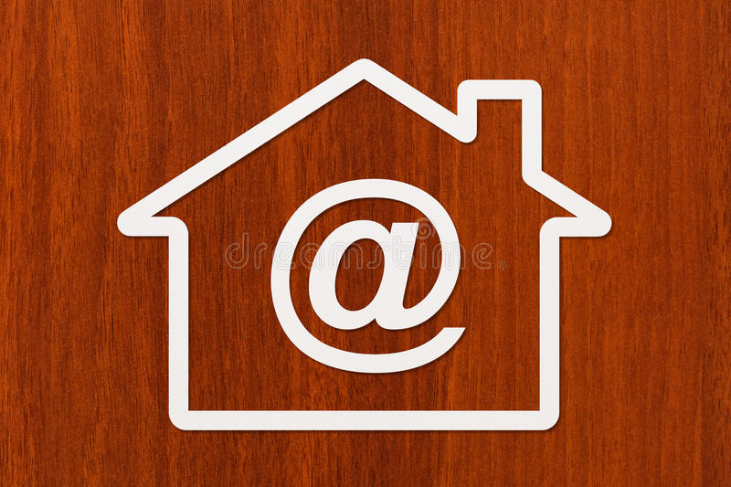 Paper house with email sign inside. Abstract conceptual image. Paper house with email sign inside on wooden background. Mortgage, credit concept. Abstract stock photos