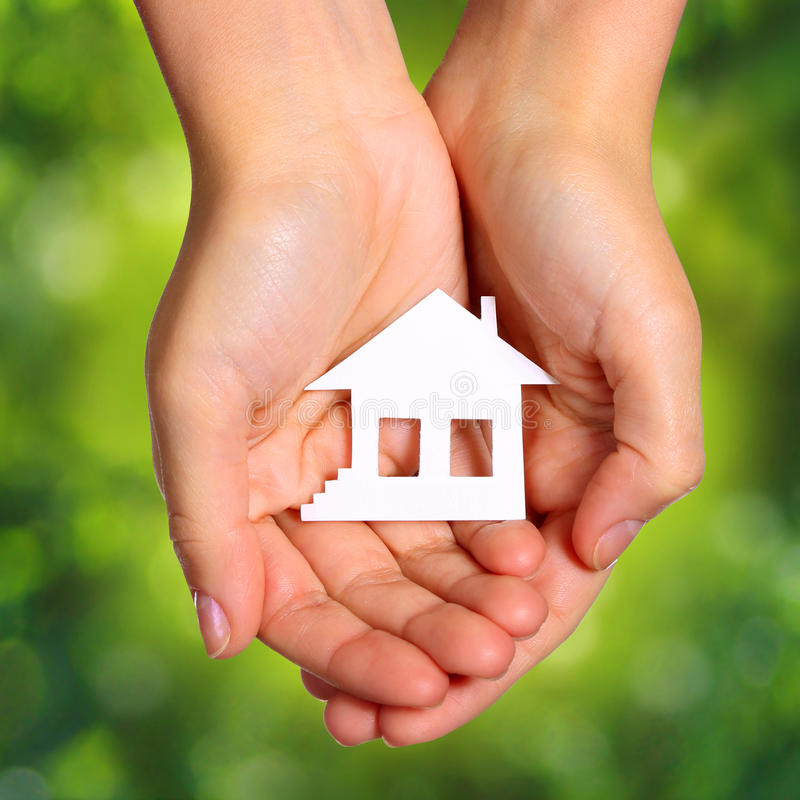 Paper House in Female Hands over Nature Green Sunny Background. royalty free stock images