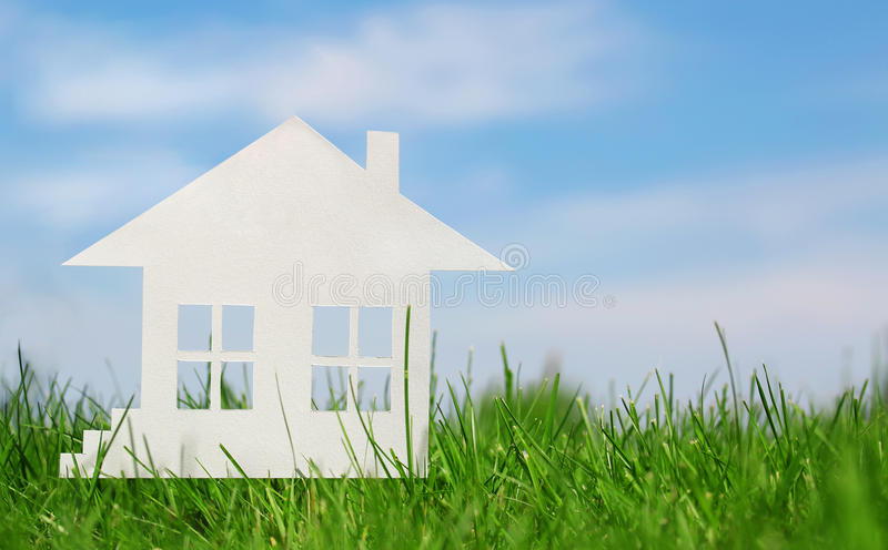 Paper house on green grass over blue sky. Concept of mortgage royalty free stock photography