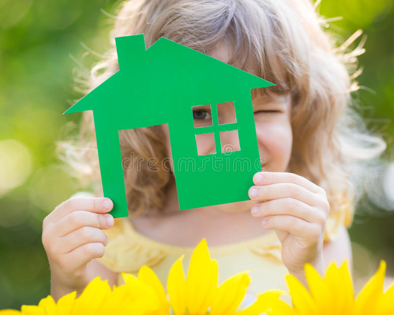 Paper house in hand. Against spring green background. Real estate concept stock photo