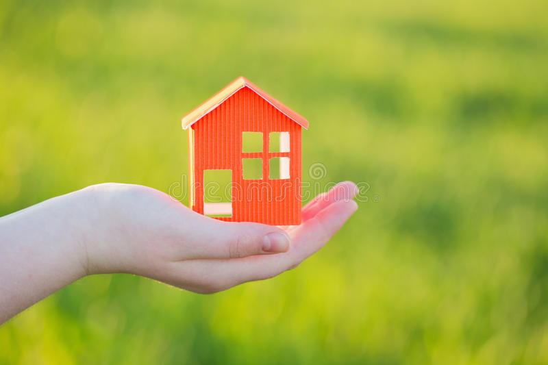 Paper house in hand outdoor. Orange paper house in hand outdoor royalty free stock photography