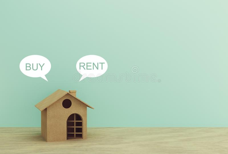 Paper house model with Buy or Rent on wood table with blue background. copy space.  stock image