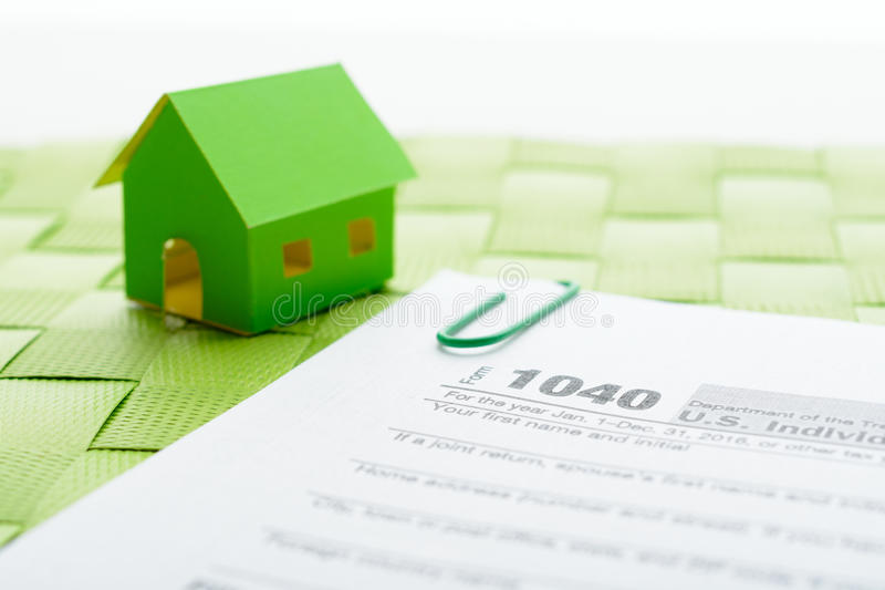 Paper house and tax form. On a green wicker mat royalty free stock images