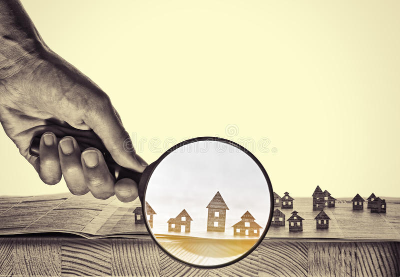 Paper house under a magnifying lens stock photography