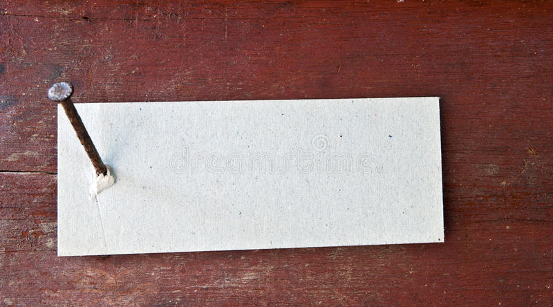 Paper label. Attached on wood wall with nail stock image