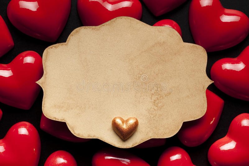 Paper label and red hearts on black background stock photography