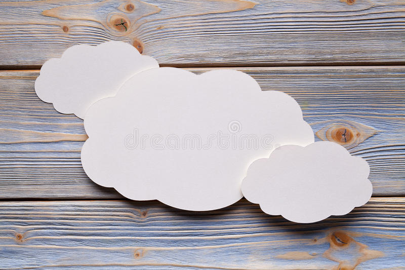 Paper label in shape of cloud on wooden background stock image
