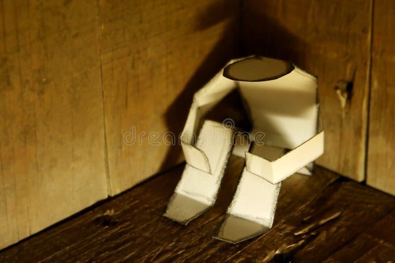 Paper man in a dark corner stock image