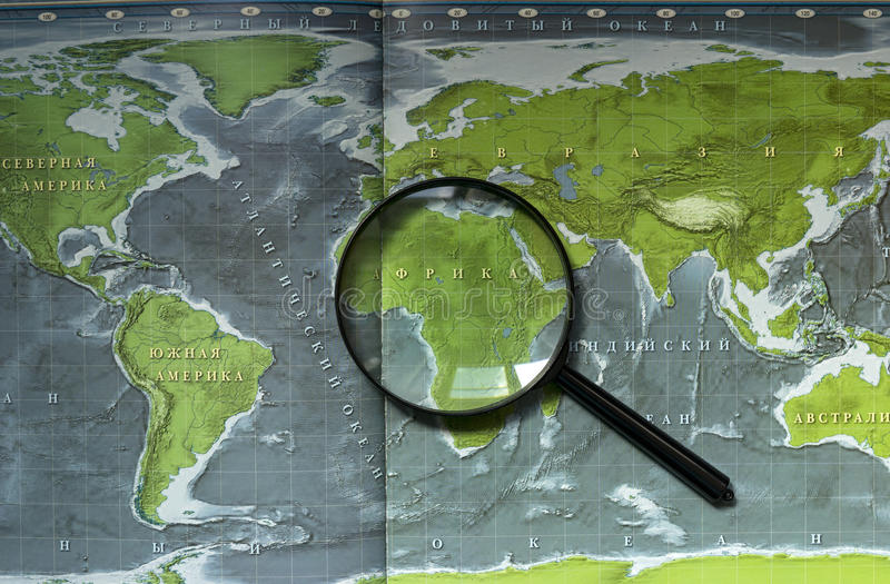 Paper map of the earth with continents, seas and oceans, magnifier. Africa, America ,Eurasia, Australia royalty free stock images