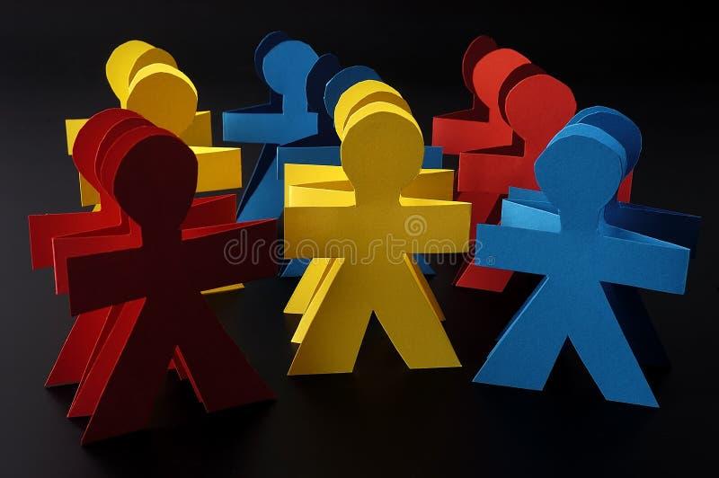 Paper men standing together. On a black back ground stock images