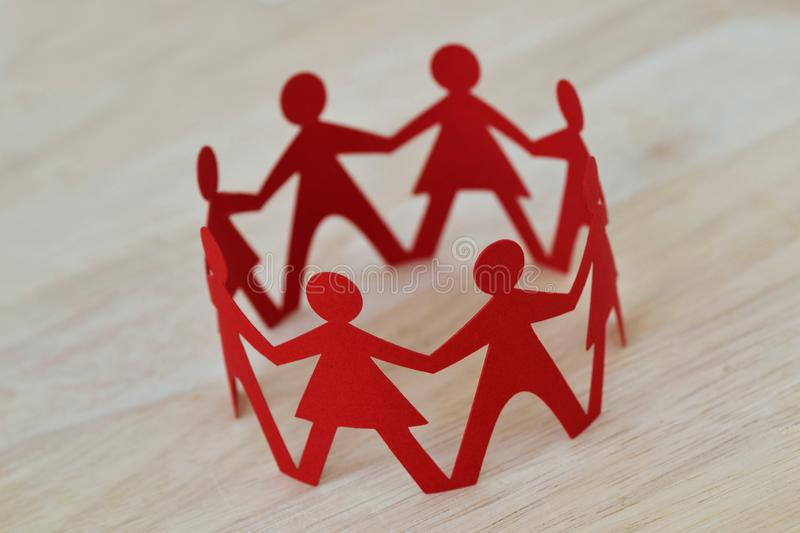 Paper men and women cut-out in a circle holding hands - Gender relationship concept. Paper men and women cut-out in a circle holding hands. Gender relationship stock images