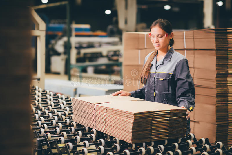 Paper mill factory worker. Box producing at a paper mill factory storage stock photo