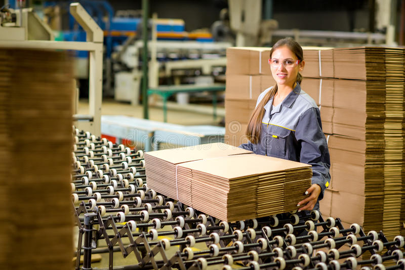 Paper mill factory worker. Box producing at a paper mill factory storage stock image