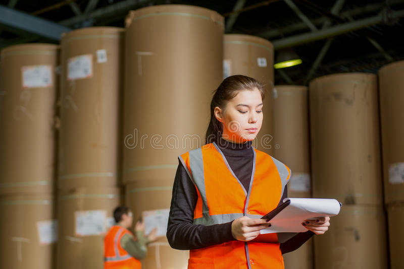Paper mill factory workers. With giant paper rolls on the background royalty free stock photo